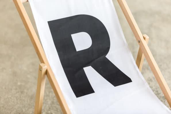 biały leżak składany z logo R